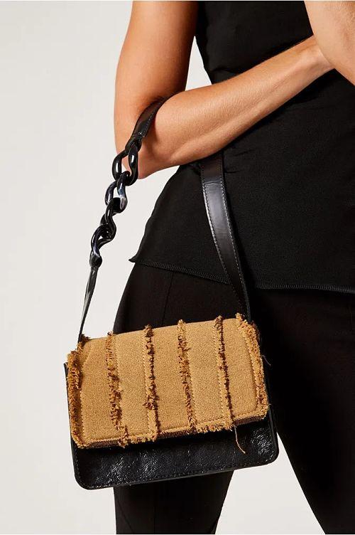 mulher segurando bolsa pequena alça de corrente coro e tecido