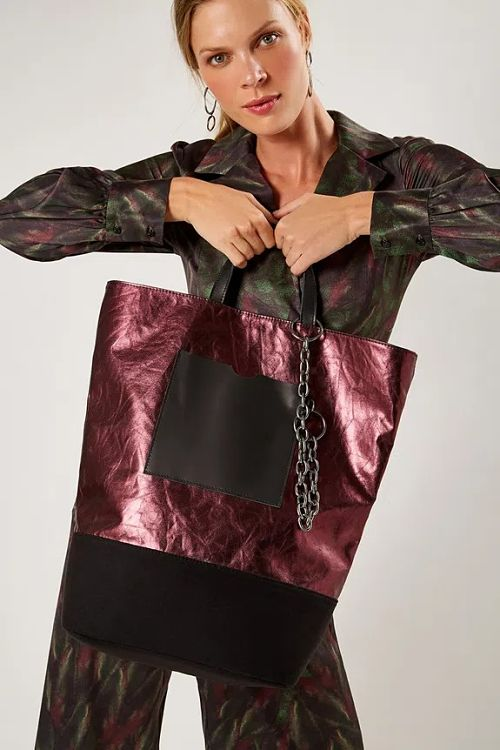 mulher segurando bolsa lateral vinho metálico