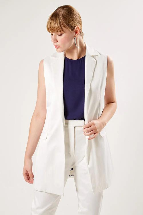 mulher com colete branco nevoa de alfaiataria olhando para baixo