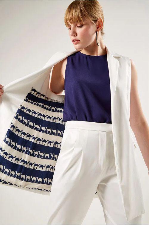 Modelo mulher vestindo Colete Alfaiataria Nevoa abrindo com a mão direita