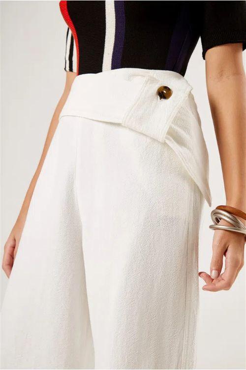 Modelo vestido calça branca e várias pulseira