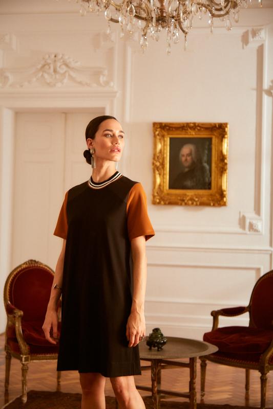 Mulher parada no meio de uma sala usando um look de sobreposição