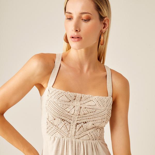 Close em mulher usando vestido cor cru bordado